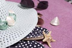 去休假在海滩 保护免受太阳和一个对的帽子太阳镜 海滩运动鞋 海星和贝壳 免版税库存图片