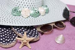 去休假在海滩 保护免受太阳和一个对的帽子太阳镜 海滩运动鞋 海星和贝壳 图库摄影