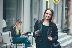 去咖啡作为 佩带在时髦的衣裳的美丽的年轻都市妇女拿着咖啡杯 免版税库存照片