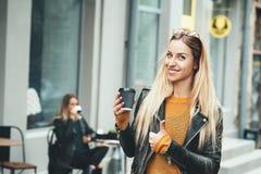 去咖啡作为 佩带在时髦的衣裳的美丽的年轻都市妇女拿着咖啡杯 免版税库存图片