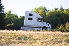 去在有绿色树的路的大半船具卡车拖拉机 库存照片