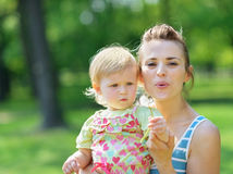 去婴孩吹的蒲公英母亲 免版税库存图片