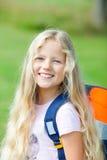 去室外学校微笑的袋子女孩 库存照片