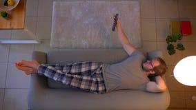 去年轻便服男性的看着电视特写镜头顶面射击关闭它和睡,当说谎在长沙发时 影视素材