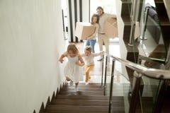 去愉快的孩子在楼上,与移动在房子里的箱子的家庭 免版税库存图片