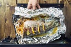 去掉从一个电烤箱的女孩一条新近地被烘烤的鳟鱼 免版税图库摄影