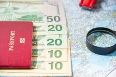 去旅行 护照、放大器、红色玩具汽车和金钱在地图 存金钱在旅行,计划对预算概念 夏天 库存图片