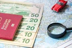 去旅行 护照、放大器、红色玩具汽车和金钱在地图 存金钱在旅行,计划对预算概念 图库摄影