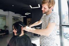 去样式的变动的 年轻美丽的妇女谈论发型与她的美发师,当坐在时 免版税库存图片