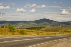 去横跨山和绿色森林的柏油路 树和他们的阴影在草 与天空蔚蓝的晴朗的夏日 ural 免版税库存照片