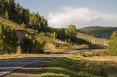 去横跨山和绿色森林的柏油路 树和他们的阴影在草 与天空蔚蓝的晴朗的夏日 ural 图库摄影