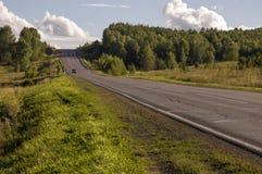 去横跨山和绿色森林的柏油路 树和他们的阴影在草 与天空蔚蓝的晴朗的夏日 ural 库存图片