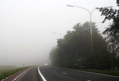 去汽车更车灯有薄雾的路 库存图片