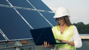 去沿它的太阳电池板和一位女性工程师与膝上型计算机 替代背景概念数字式能源例证太阳风 股票录像
