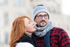 去深色的妇女亲吻人 看对人面孔的红色头发妇女 夫妇愉快的纵向 玻璃的有胡子的人 免版税图库摄影