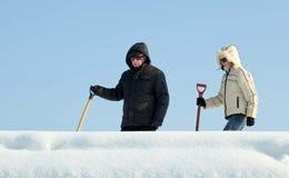 去的人们从屋顶取消雪 免版税库存照片