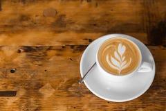去的咖啡在与拿铁艺术的木桌上 街道咖啡 复制空间 库存图片