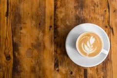 去的咖啡在与拿铁艺术的木桌上 街道咖啡 顶视图 库存照片