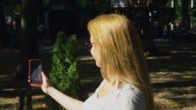 去的妇女停放与她的电话夏日在太阳光下 4k,慢镜头, standicam射击 股票视频