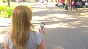 去的妇女停放与她的电话夏日在太阳光下 4k,慢镜头, standicam射击 股票录像