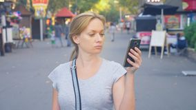 去的妇女停放与她的电话夏日在太阳光下 4k,慢镜头, standicam射击 影视素材