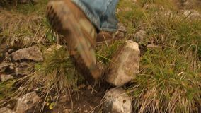 去的徒步旅行者的脚小山和击落在足迹的岩石 影视素材
