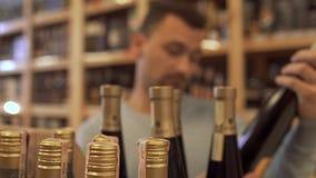 去的顾客读酒的构成在瓶标签,点头满意和拿走酒瓶 股票视频
