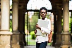 去类 在校园背景的年轻美丽的美国黑人的妇女藏品膝上型计算机 大学,技术,企业概念 库存图片