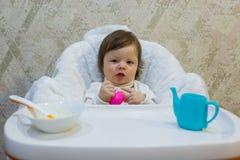 去逗人喜爱的小孩的女孩坐在哺养的婴孩椅子和哺养粥 免版税库存图片