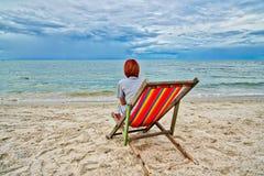 去野餐和俯视海的妇女坐一把红色椅子在海滩 库存照片