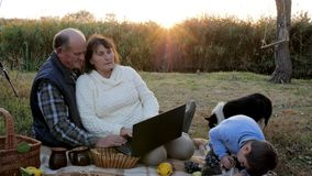 去野餐在日出,有吸引力的成熟加上孙子,并且宠物坐在有膝上型计算机的格子花呢披肩 股票录像