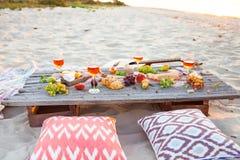去野餐在海滩在boho样式的日落 浪漫晚餐,朋友 免版税库存图片