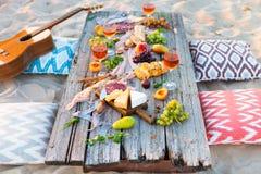 去野餐在海滩在boho样式的日落 浪漫晚餐,朋友 库存照片