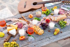 去野餐在海滩在boho样式的日落 浪漫晚餐,朋友 图库摄影