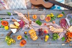 去野餐在海滩在boho样式的日落 浪漫晚餐,朋友 免版税图库摄影
