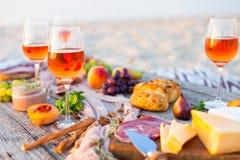 去野餐在海滩在boho样式的日落 浪漫晚餐,朋友 库存图片