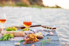 去野餐在海滩在boho样式的日落 浪漫晚餐,朋友 免版税库存照片