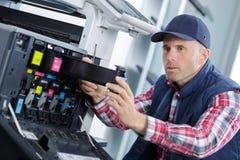 去除弹药筒容器的打印机技术员 免版税库存图片