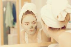 去除面部黏土泥面具的妇女在卫生间里 库存照片