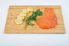 去骨切片熏制的鳟鱼用新鲜的草本和柠檬在委员会 海鲜,被隔绝 免版税库存照片