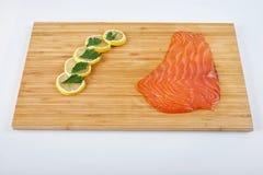 去骨切片熏制的鳟鱼用新鲜的草本和柠檬在委员会 海鲜,被隔绝 免版税库存图片