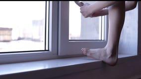 参与体操无法认出的ittle女孩由窗口投入她的芭蕾舞鞋在一个现代徒有其表演播室 ? 影视素材