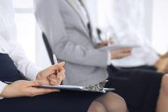 参与在会议或训练在办公室,特写镜头的商人 坐椅子和做笔记象的妇女 库存照片