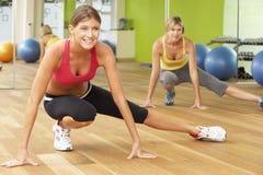 参与在健身房健身类的两名妇女 免版税图库摄影