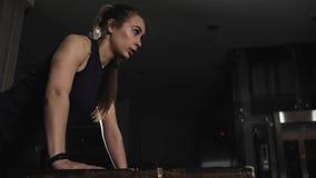 参与在健身房的晚上年轻体育女孩 做从长凳的一个锻炼俯卧撑 股票视频
