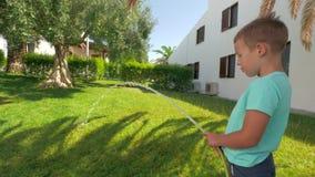 参与在家庭责任和浇灌绿色草坪的孩子由房子 股票录像