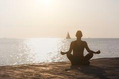 参与在日出的瑜伽在与风船的海滩一个年轻运动女孩的剪影 免版税库存照片