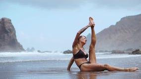 参与在海洋的体操妇女坐麻线并且在水附近执行桥梁反对波浪和 影视素材