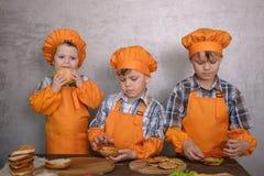 参与烹调自创汉堡服装厨师的三个逗人喜爱的男孩 免版税图库摄影
