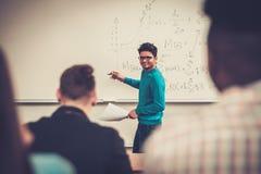 参与活跃教训的多民族小组快乐的学生,当坐在教室时 免版税库存照片